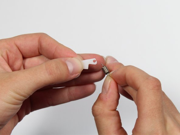 Using two hands, remove the spring from the plastic tabs.