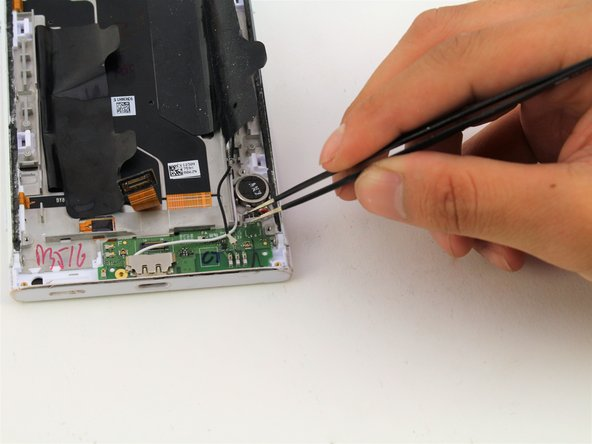 Grab the vibration motor connected to the charging port PCB board with your flathead tweezers.