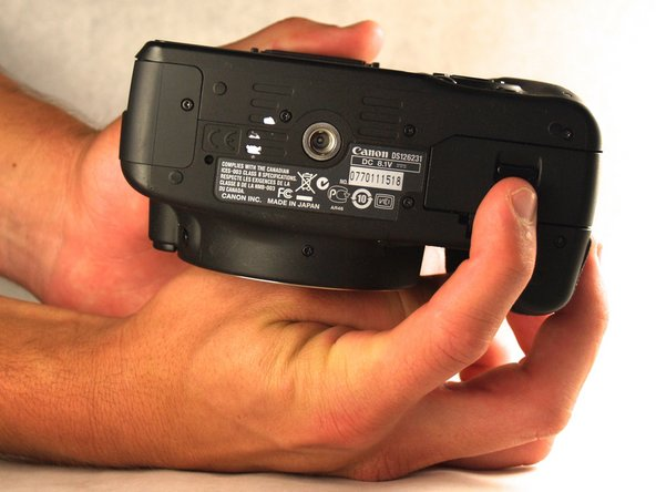 Find the bottom of the device and use your fingers to push down on the latch on the battery door.