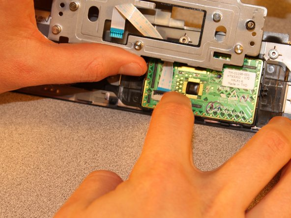 Disconnect the ribbon cable from the receptacle on the touchpad circuit board. The ribbon cable will not fall away because it is glued to the bracket that holds the touchpad in place