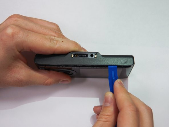 Take the iFixit opening tool and place it between the crevice as shown.