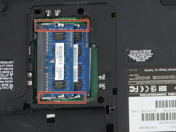 Take a nylon spudger and push the prongs so that it releases the RAM.