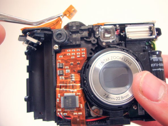 Pull the electric strip off of the top of the camera with tweezers.