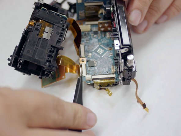 Using your tweezers, remove the two ribbon cables connecting the lens assembly to the motherboard.