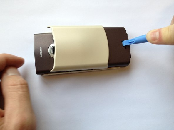 Image 1/1: Press the button with the plastic opening tool and slide the back case downward relative to the phone.