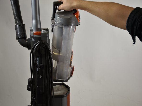 Grab the handle of the  dust cup, then pull up and away from the vacuum.