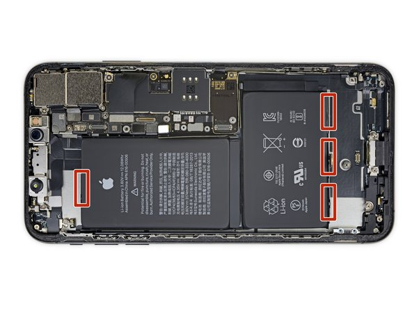 The battery is secured to the rear case by four pieces of stretch-release adhesive—one on the top cell, and three on the bottom.