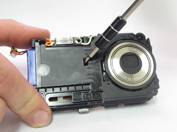 On the front of the camera locate the small rectangular slot where the battery is exposed.