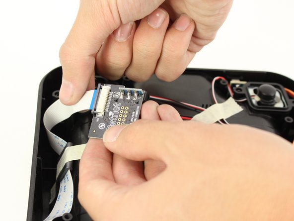 Pull the ribbon connector out of its slot using one hand and another hand on the base of the charging assembly.