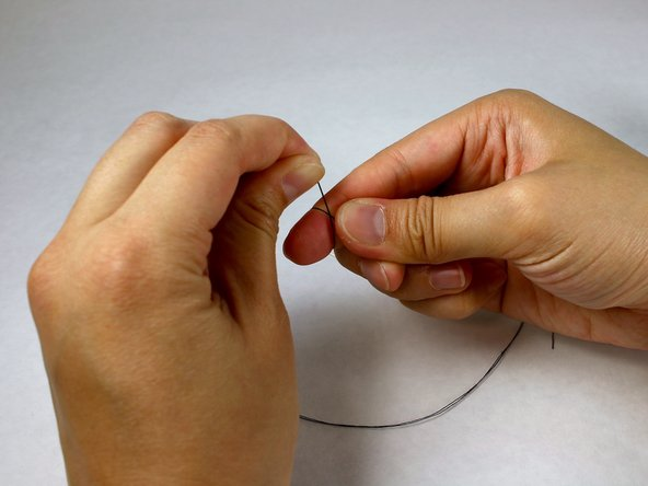 Image 1/3: Pinch the ends of the thread between your index finger and thumb and roll your index finger downwards until the loop slips off.