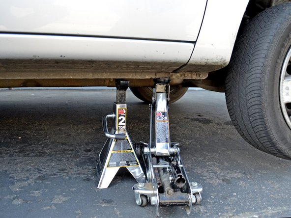 Image 1/2: Slowly lower the jack until the jack stand is supporting the car. Remove the jack.