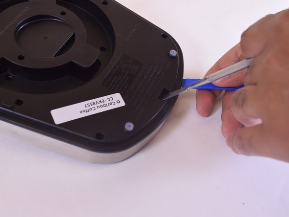 With the metal tool still inserted, use an opening tool between the black and silver sides to pry the base open.
