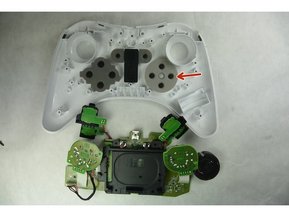 Remove the motherboard and connected components. The rubber pad of the D Pad is indicated in the image by the red arrow.