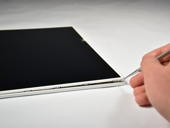 Insert the metal spudger into the groove on the edge of the screen.