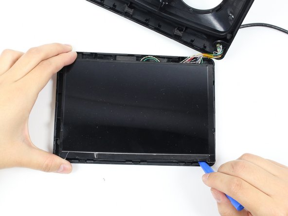 Run the plastic opening tool along the bottom edge under the LCD screen to separate the adhesive holding the LCD to the display box.