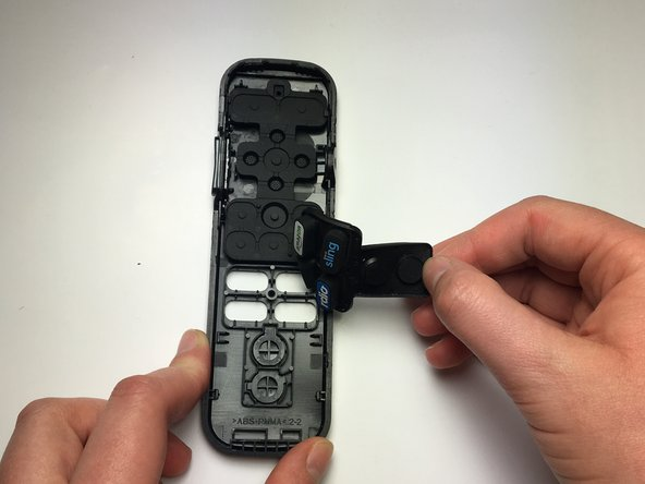Remove the button panels by gripping the bottom edge and pulling upward until the panel is no longer in contact with the remote cover.
