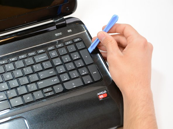 Taking plastic opening tools in hand, carefully and gently pry open the outer perimeter of the keyboard.