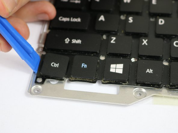 To replace an individual key, remove the key from the keyboard using a plastic opening tool.