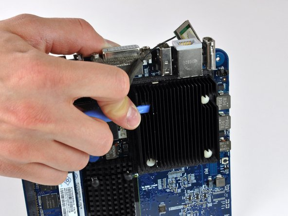 Image 1/2: Using a plastic opening tool (or similar) in one hand, push down one pin holding the heat sink on the logic board. The spring under the pin will provide moderate resistance.