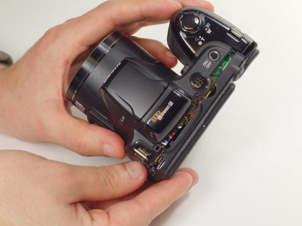 Carefully detach the back side of the camera by lifting both ends, with moderate force wobble until loosened enough to remove.