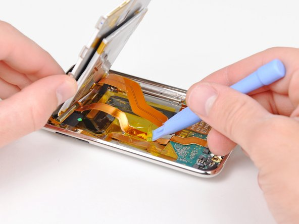 Image 1/1: Use the edge of an iPod opening tool to remove the piece of tape covering the display data cable.