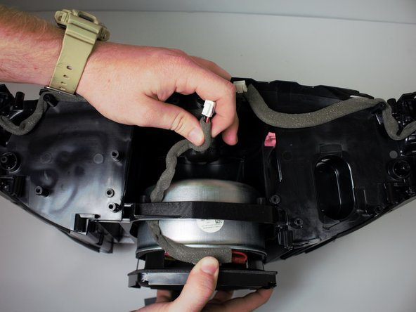 Remove the subwoofer by pulling towards the back of the device while tucking the wire under the plastic enclosure.