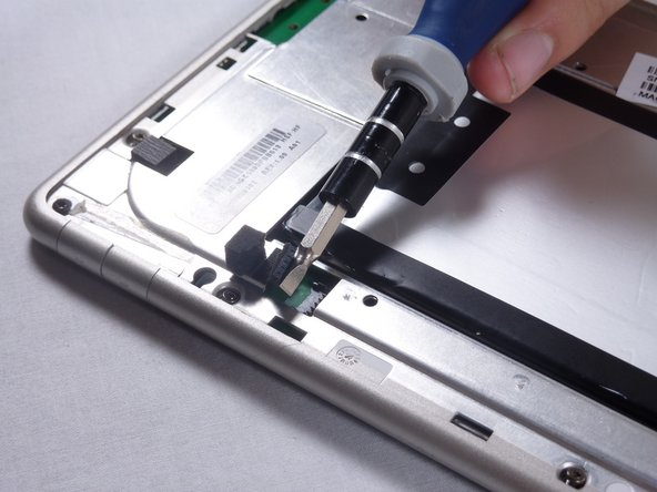 Use a spudger or plastic opening tool to disconnect the battery cable from the motherboard.
