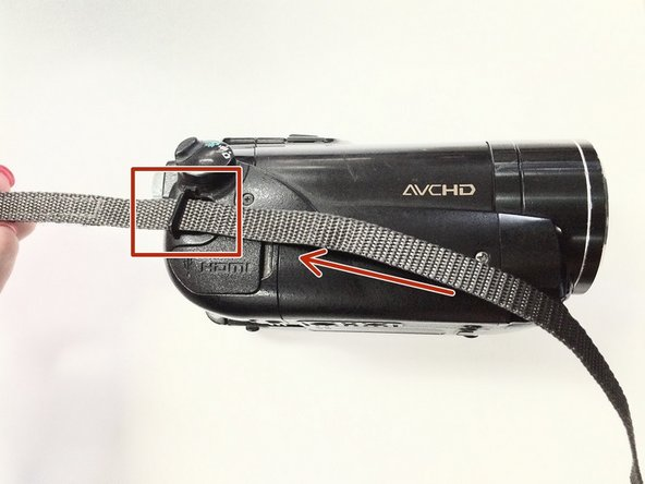 Re-insert the new Velcro strap through the back anchor hole in the direction of the arrow (toward the battery end of the camcorder).