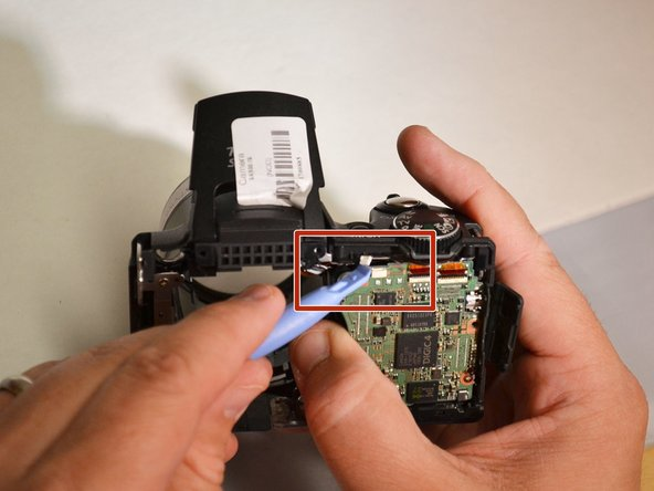 Using the plastic pry tool, remove the motherboard and the flash unit from camera frame (Motherboard and flash unit are separated from camera).