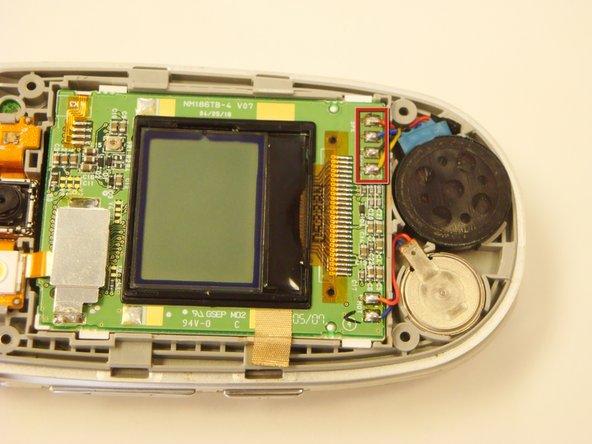 Localisez les quatre joints de soudure (connectés aux fils jaune, noir, bleu et rouge) sur la partie inférieure du téléphone, connecté à l'enceinte. Il apparaîtra comme une partie circulaire noire avec quelques trous.