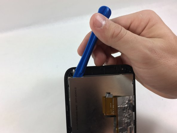 Image 3/3: Using a plastic opening tool, apply light lifting pressure to each of the 6 casing clips to release the screen from the plastic casing.