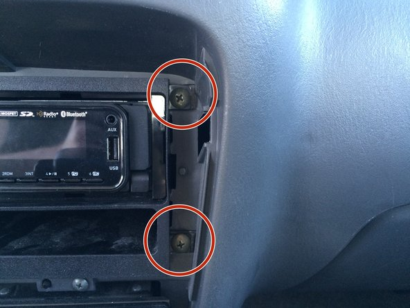 Once the trim is removed, remove the four screws found on each corner of the stereo.