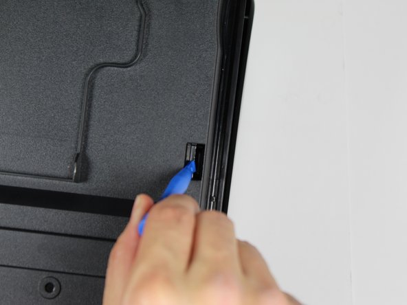 Use a plastic opening tool to snap off the right-side clip and push the clip outward.