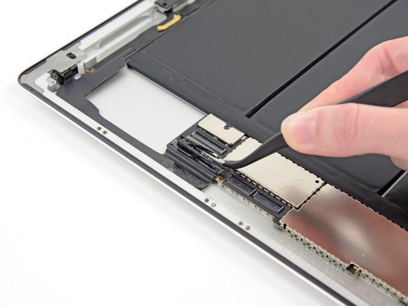 Use tweezers to peel back and remove the piece of electrical tape covering the headphone jack assembly cable connector.