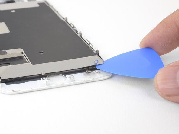 Insert an opening pick from the bottom right corner and continue to separate the display cable from the LCD shield plate.