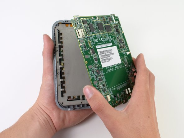 Image 1/3: Though the device has proven very simple to take apart, we do note that all of the components are held on with a lot of adhesive. We have not had to use a [product|IF145-031|heat gun] yet, but we tread carefully as we remove the heavily adhered motherboard from the frame.