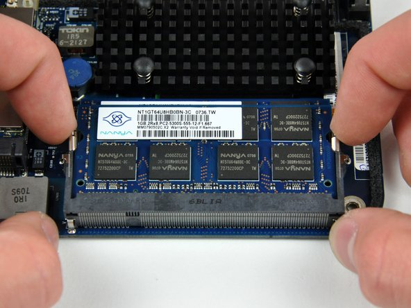 "Simultaneously pull the tabs on each side of the RAM chip away from the center of the chip. These tabs lock the chip in place and releasing them will cause the chip to ""pop"" up."