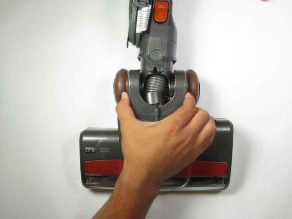 Grab the vacuum on both sides of the hose and pull up to remove the top of the vacuum halfway.