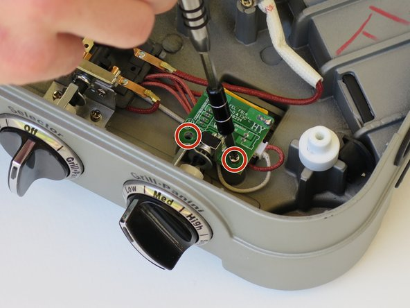 Remove the two 6 mm Phillips #2 screws that secure the knob circuit board.