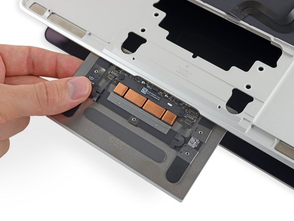 Hinge open the display just slightly to free the trackpad assembly from the upper case, and remove the trackpad assembly.
