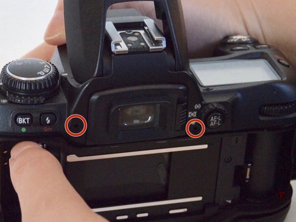 Two of the screws are located by the viewfinder and and the other two are on each side of the camera.