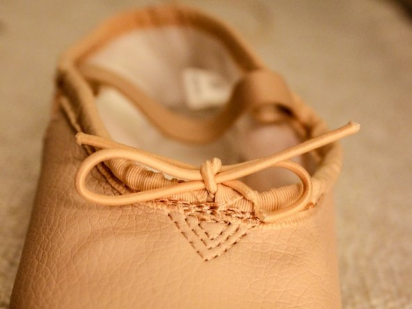Once elastic is evenly pulled through the ballet casing, secure the knot and cut the leftover elastic, if necessary