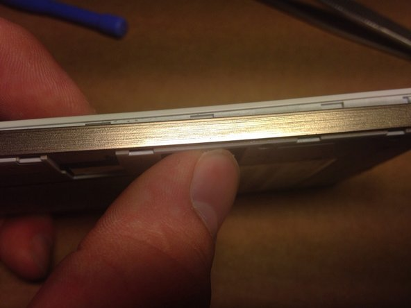 Insert a spudger between the aluminium back cover and the front panel and pry the back cover loose.