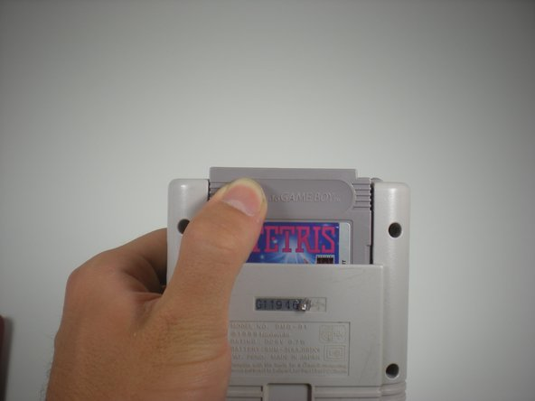 Image 1/1: Remove cartridge by placing thumb on the outside of the cartridge near the indentation and pushing up. Dislodging the cartridge from the cartridge reader.