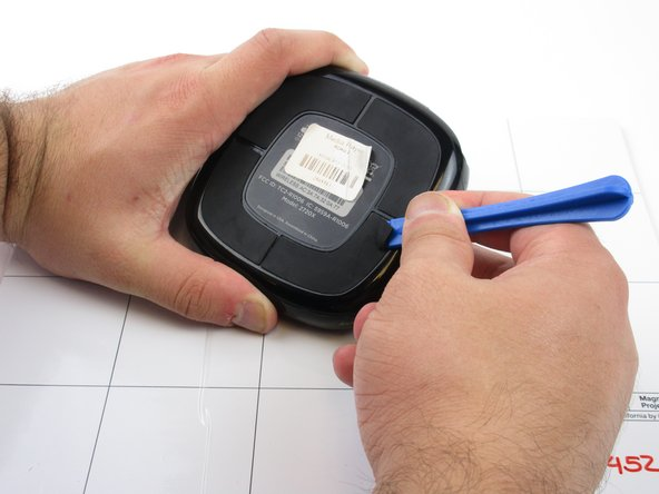 Gently use the plastic opening tool to pry the rubber pads off.