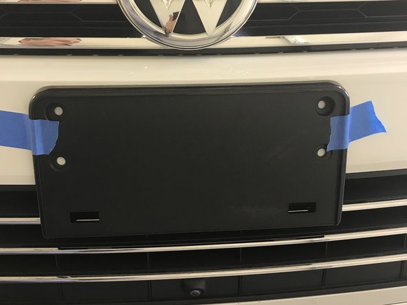 Position the license plate frame and center it on the VW emblem and parking camera (below, if installed). You can use the vertical supports in the lower grill (hard to see in this pic) to assist in alignment.