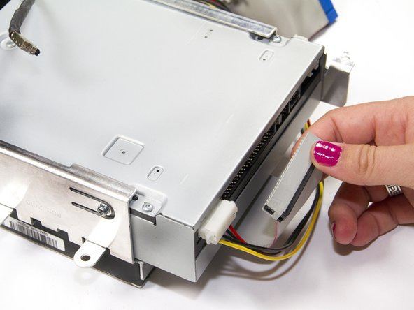 Unplug the ribbon cable from the optical drive by grasping the plastic base of the connector and wiggling it gently.