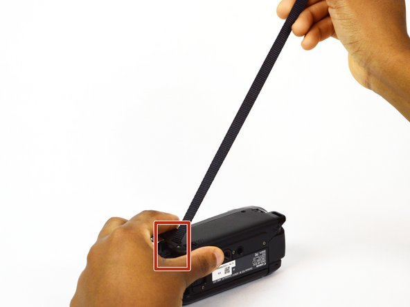 Pull the strap through the slot on the left side of the camcorder.
