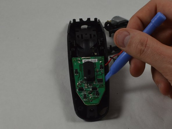 Use the plastic opening tool to remove the motherboard from its housing.