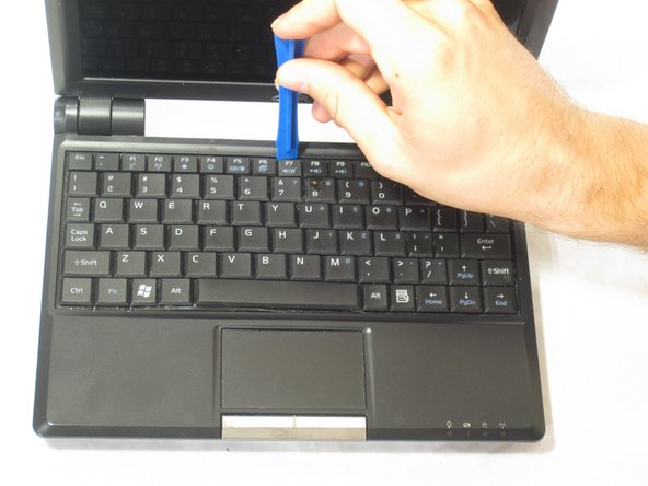 Use the plastic opening tool to lift up the keyboard.